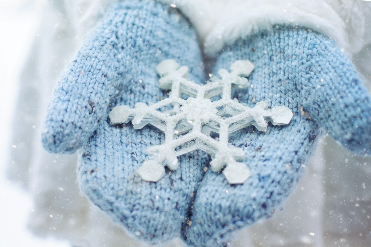 A woman wearing blue mittens holding a large snowflake