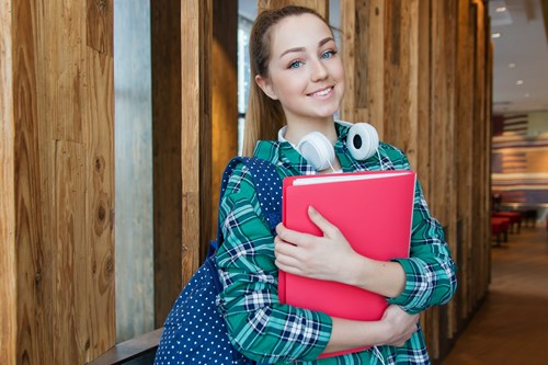 A photo of a smiling female student holding a red folder