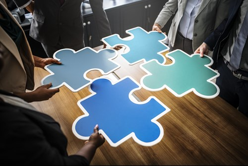 People standing around a table, slotting large jigsaw pieces together